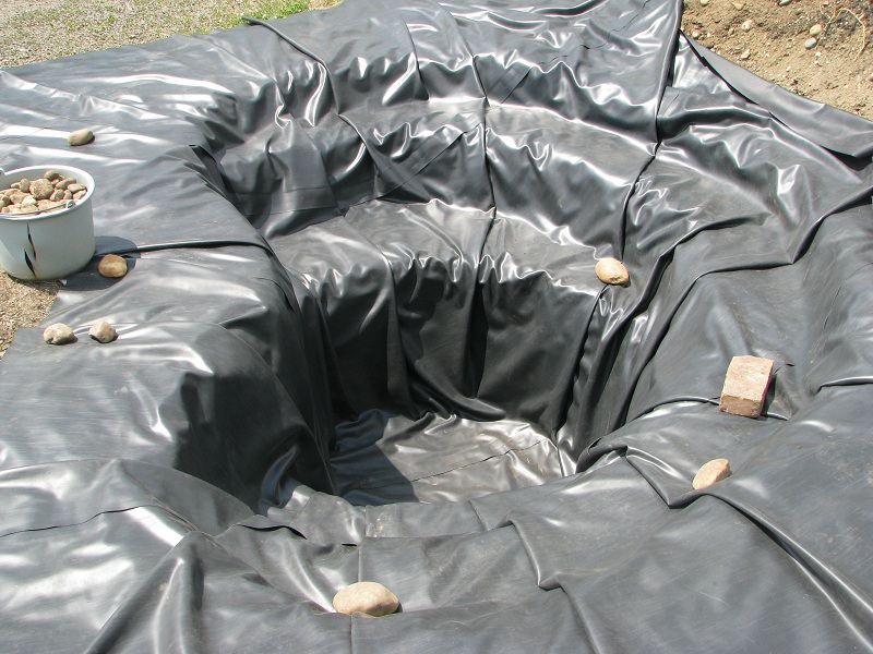 Lágy PVC tófólia tómederbe fektetése